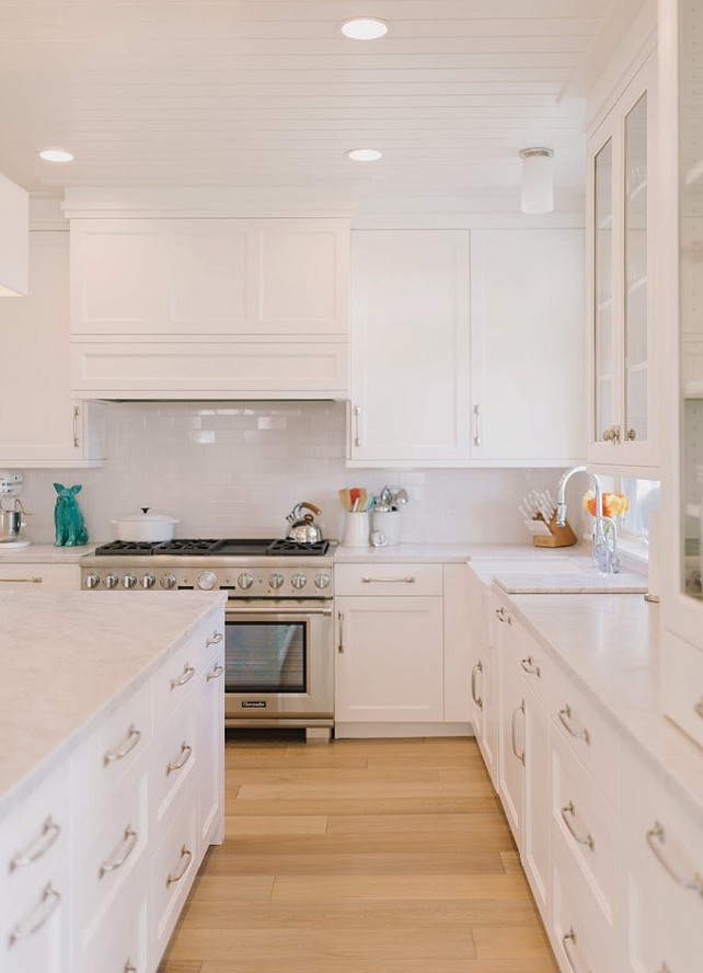 White Kitchen. White kithen with hardwood floors, white cabinets, white marble countertop. white subway tile backsplash and beadboard ceiling. #WhiteKitchen #Kitchen   Four Chairs Furniture.