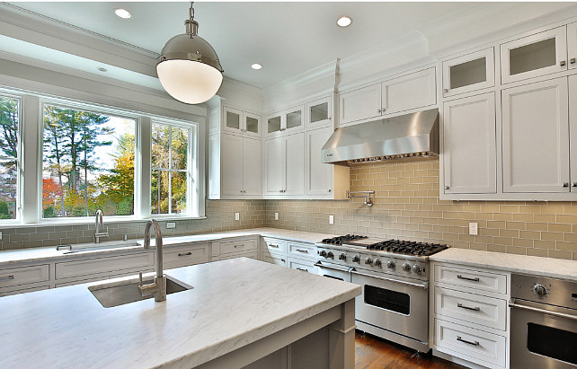 White kitchen with gray subway tile backsplash and honed white marble countertop. White and Gray Kitchen. Blue Water Home Builders.
