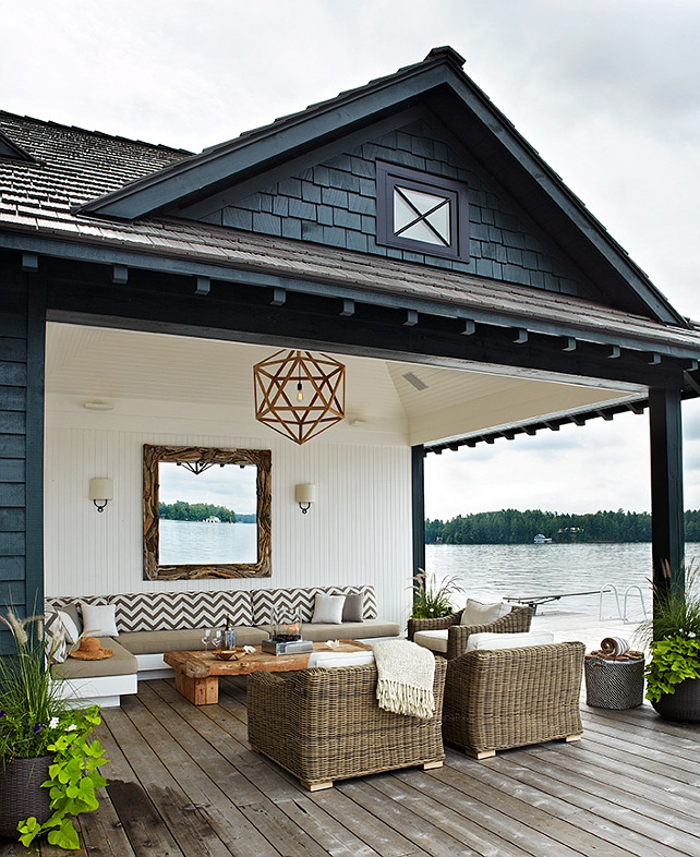 Lakeside Covered Patio.  Lakeside cottage covered deck with beadboard ceiling and wood polyhedron pendant. White beadboard walls with rectangular driftwood mirror flanked by iron ring sconces with half moon shades. Outdoor sectional sofa upholstered in white and tan chevron cushions. Driftwood coffee table, wicker outdoor chairs and plank deck floors.  Anne Hepfer Designs.